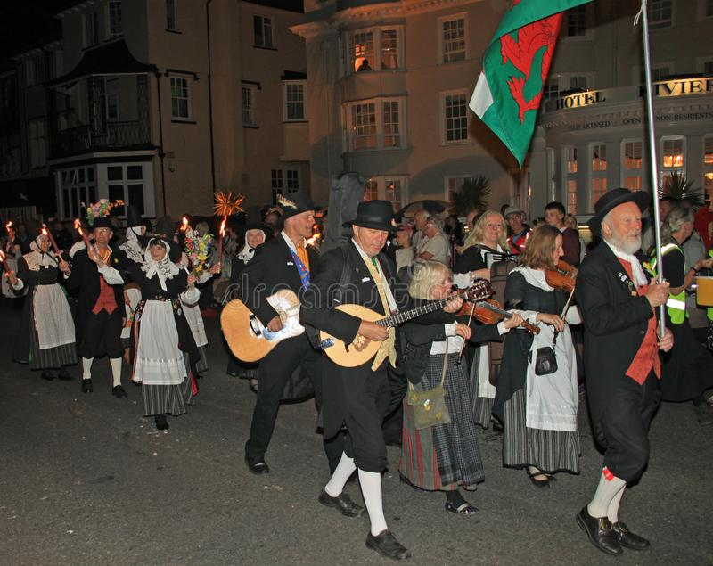 SIDMOUTH, DEVON, ENGLAND - AUGUST 10TH 2012: A group of Welsh performers takes part in the night time closing procession of folk royalty free stock photo