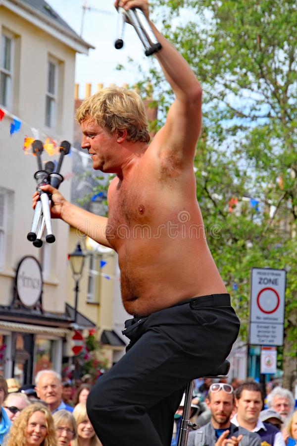 SIDMOUTH, DEVON, ENGLAND - AUGUST 5TH 2012: A street juggler takes the applause from an appreciative crowd after using flaming royalty free stock image