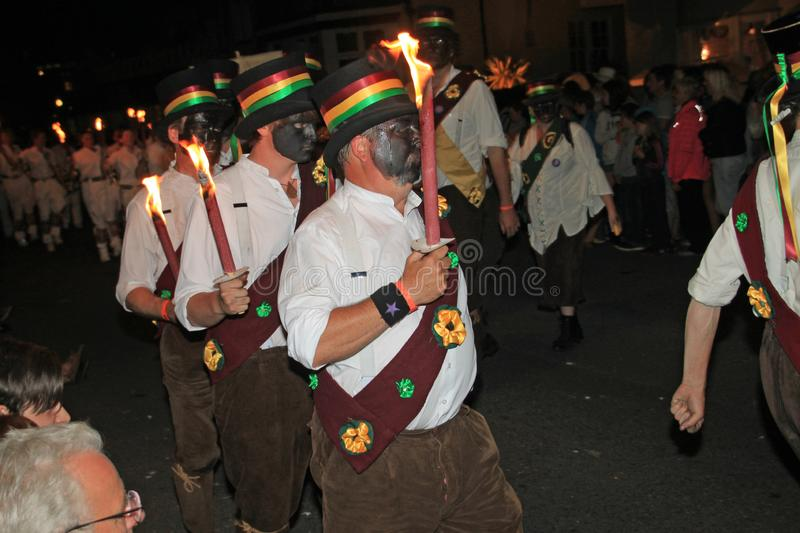 SIDMOUTH, DEVON, ENGLAND - AUGUST 10TH 2012: A troup of traditional English Morris dancers holding flaming torches takes part in. The night time closing stock images