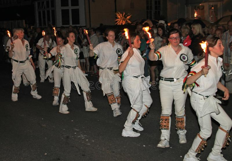 SIDMOUTH, DEVON, ENGLAND - AUGUST 10TH 2012: A troup of young lady Morris dancers hold their flaming torches as they takes part in. The night time closing stock photo