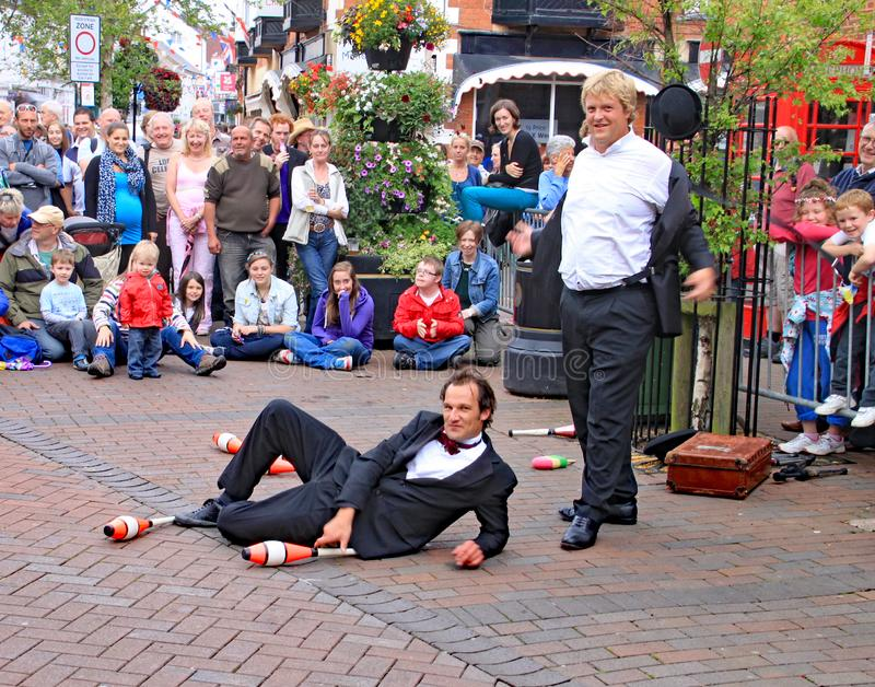 SIDMOUTH, DEVON, ENGLAND - AUGUST 5TH 2012: Two street jugglers and entertainers perform in the town square to an appreciative. Audience stock photography