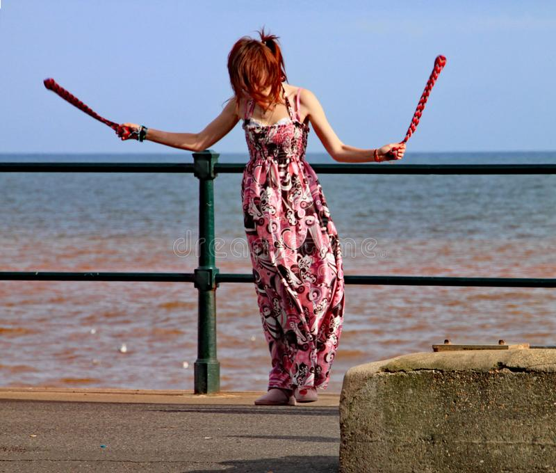 SIDMOUTH, DEVON, ENGLAND - AUGUST 5TH 2012: A young woman entertains passers by with twirling clubs by the iron railings of the royalty free stock photography