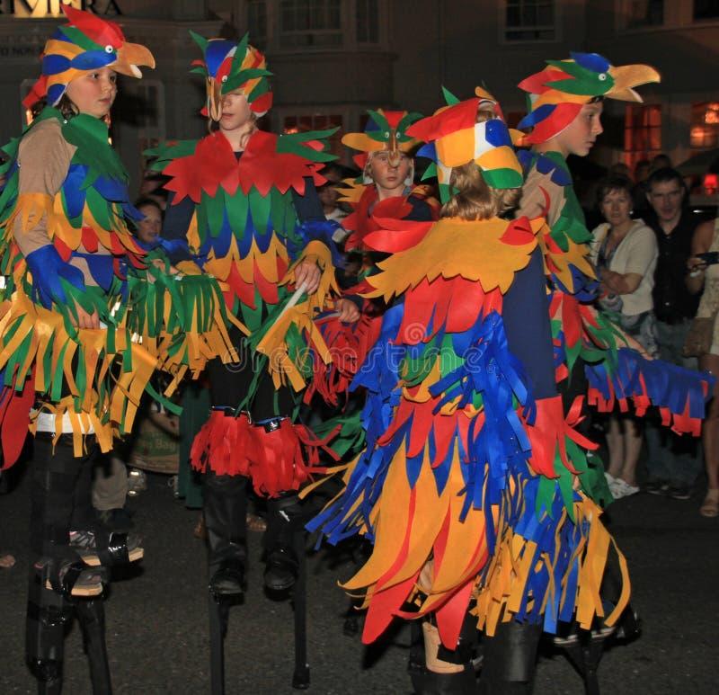 SIDMOUTH DEVON, ENGLAND - AUGUSTI 10TH 2012: Barn som är utklädda som färgglade papegojor och att gå på styltor, tar delen i natt royaltyfri foto