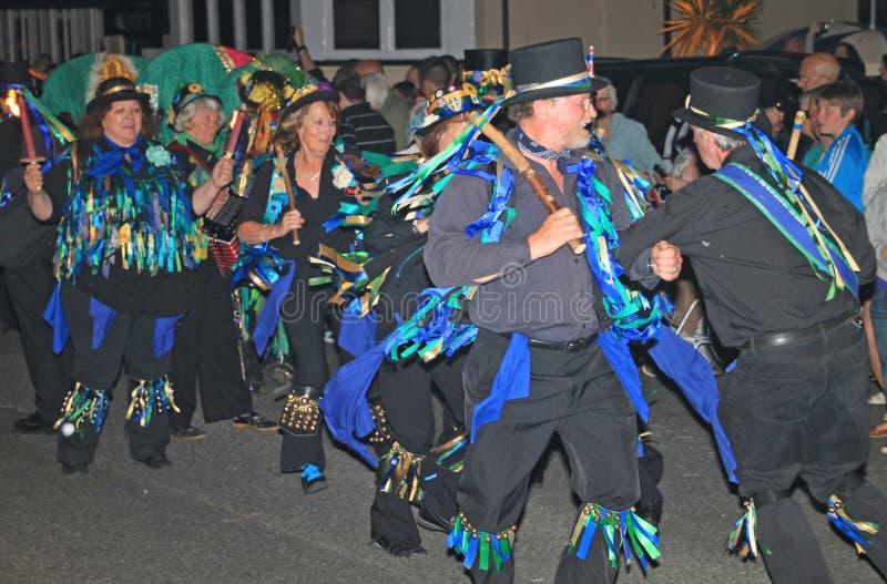 SIDMOUTH DEVON, ENGLAND - AUGUSTI 10TH 2012: En grupp av iklädda dekorerade bästa hattar för Morris dansare och trasiga blåa wais royaltyfri fotografi