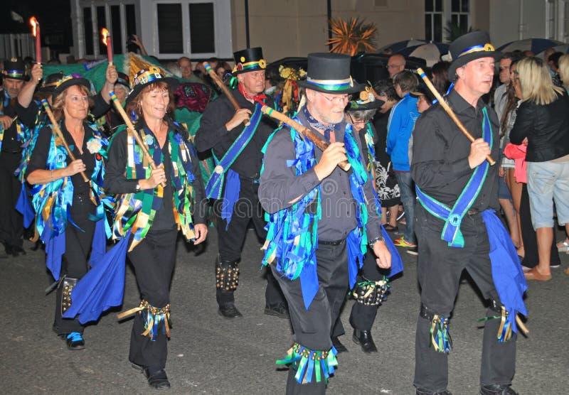 SIDMOUTH DEVON, ENGLAND - AUGUSTI 10TH 2012: En grupp av iklädda dekorerade bästa hattar för Morris dansare och trasiga blåa wais royaltyfri foto
