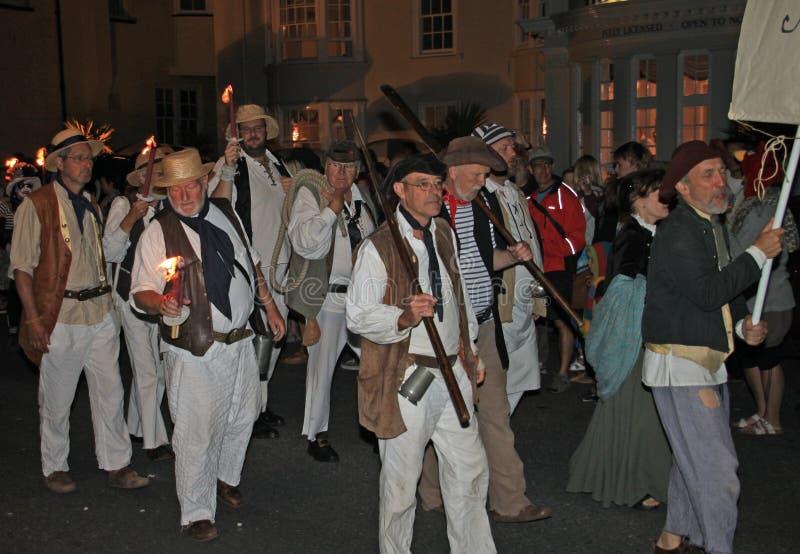 SIDMOUTH DEVON, ENGLAND - AUGUSTI 10TH 2012: En grupp av klädde män, som piratkopierar, tar delen i nattetidbokslutprocessionen a royaltyfri foto