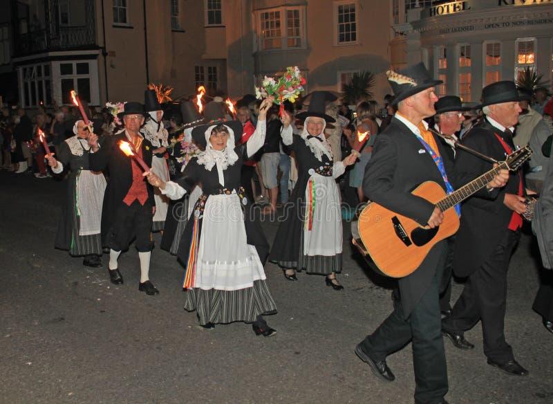 SIDMOUTH DEVON, ENGLAND - AUGUSTI 10TH 2012: En grupp av walesiska aktörer tar delen i nattetidbokslutprocessionen av folk fotografering för bildbyråer