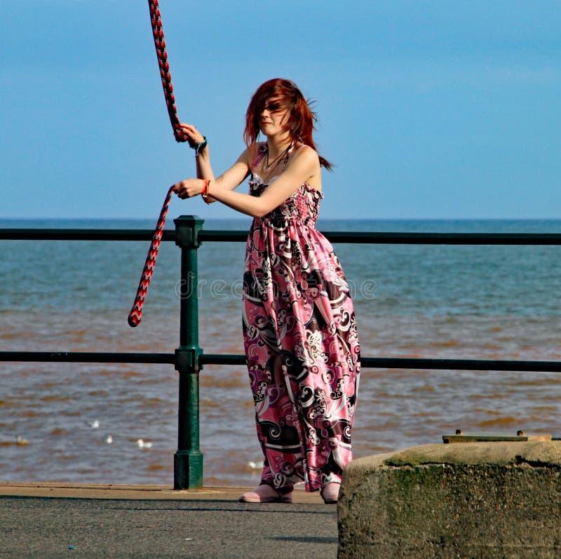 SIDMOUTH DEVON, ENGLAND - AUGUSTI 5TH 2012: En ung kvinna underhåller förbipasserande förbi med att snurra klubbor vid järnräcken fotografering för bildbyråer