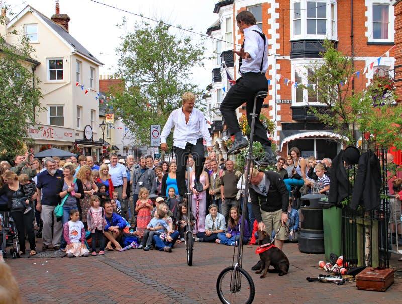 SIDMOUTH DEVON, ENGLAND - AUGUSTI 5TH 2012: Två gatajonglörer och underhållare utför i stadfyrkanten till ett tacksamt royaltyfri foto