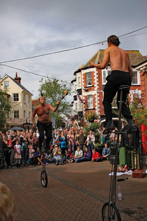 SIDMOUTH DEVON, ENGLAND - AUGUSTI 5TH 2012: Två gatajonglörer och underhållare utför med enhjulingar och brandklubbor i staden arkivfoton