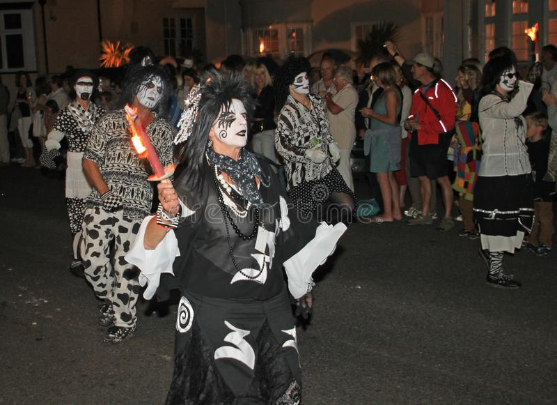 SIDMOUTH, DEVON, INGHILTERRA - 10 AGOSTO 2012: Un troup di ballo vestito in costumi in bianco e nero molto sinistri partecipa all fotografie stock libere da diritti