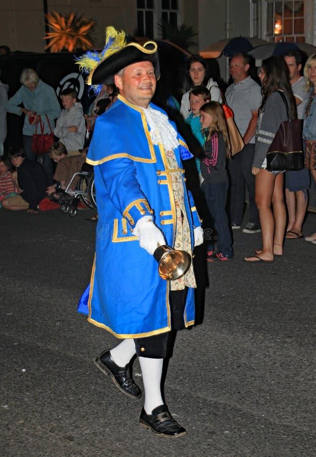 SIDMOUTH, DEVON, INGLATERRA - 10 DE AGOSTO DE 2012: O crier de cidade conduz a noite que fecha para baixo a procissão ao longo da imagens de stock
