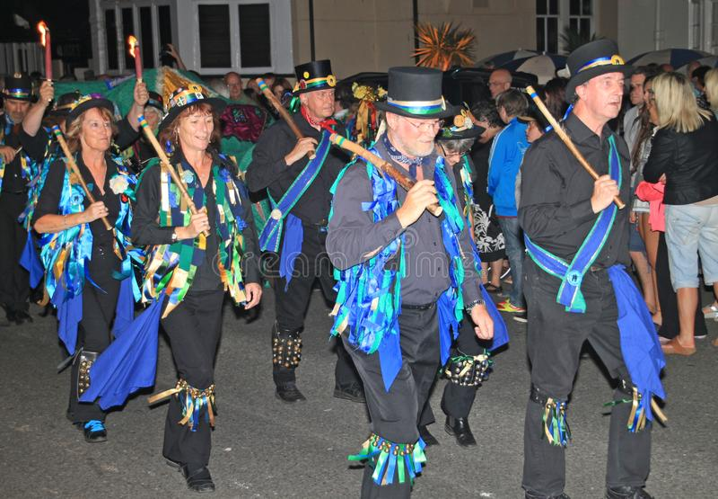 SIDMOUTH, DEVON, INGLATERRA - 10 DE AGOSTO DE 2012: Um grupo de dançarinos de Morris vestidos em chapéus altos decorados e em wai foto de stock royalty free