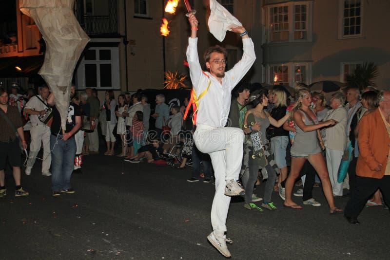 SIDMOUTH, DEVON, INGLATERRA - 10 DE AGOSTO DE 2012: Um homem novo muito energético vestiu tudo no branco e em guardar um pano e u foto de stock