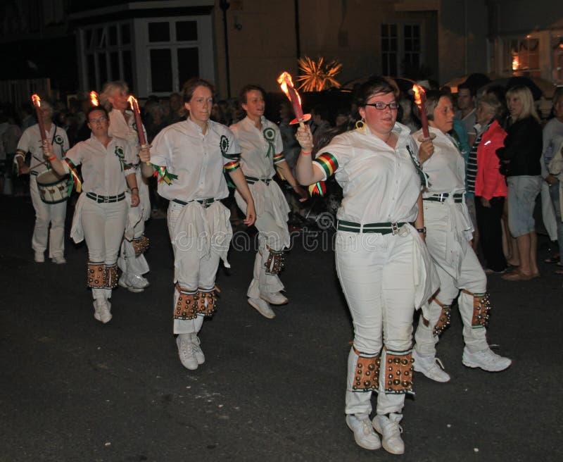 SIDMOUTH, DEVON, INGLATERRA - 10 DE AGOSTO DE 2012: Um troup de dançarinos de Morris da jovem senhora guarda suas tochas flamejan fotos de stock