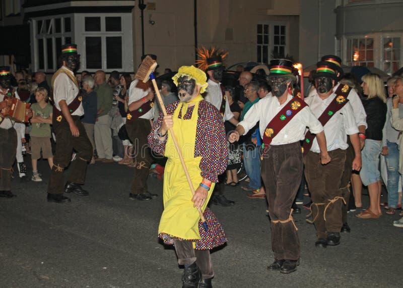 SIDMOUTH, DEVON, INGLATERRA - 10 DE AGOSTO DE 2012: Um troup de dançarinos de Morris ingleses tradicionais conduziu por um homem  imagem de stock