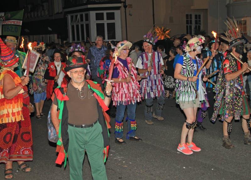 SIDMOUTH, DEVON, INGLATERRA - 10 DE AGOSTO DE 2012: Un grupo de bailarines de Morris vestidos en sombreros florecidos y los chale imagenes de archivo