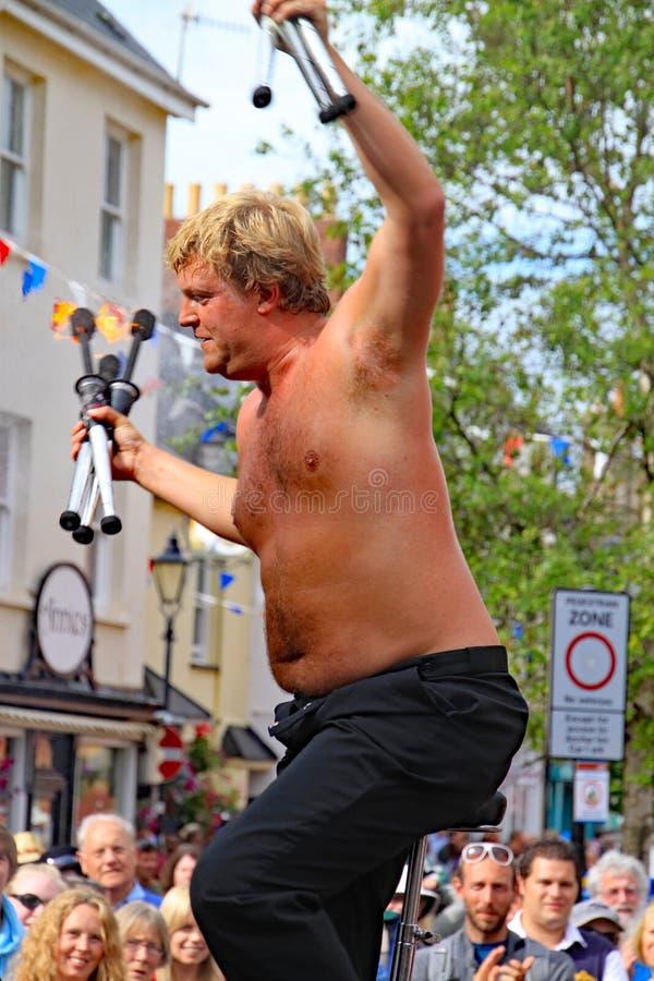 SIDMOUTH, DEVON, INGLATERRA - 5 DE AGOSTO DE 2012: Un juglar de la calle toma el aplauso de una muchedumbre elogiosa después de u imagen de archivo libre de regalías