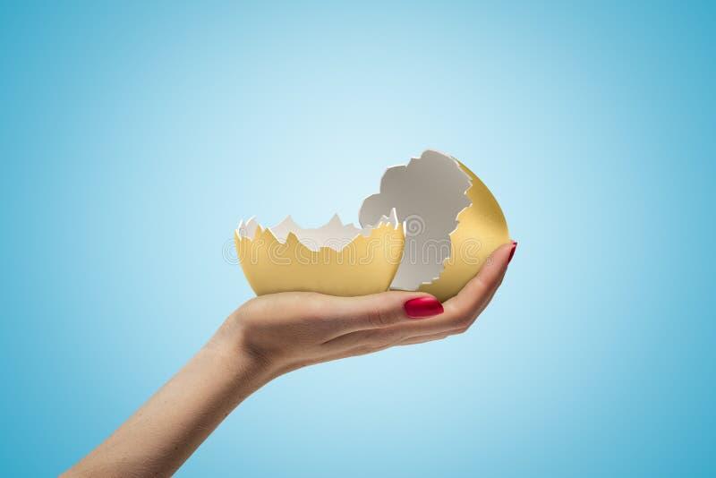 Sidocloseup av kvinnas hand som vänder mot upp och rymmer två delar av den tomma guld- äggskalet på ljust - blå lutningbakgrund arkivfoto