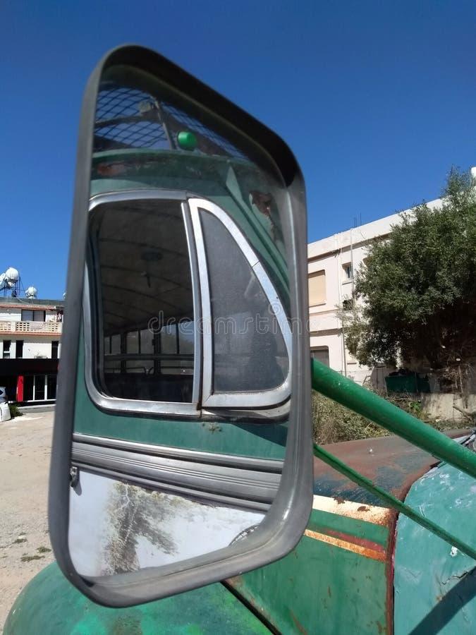 Sidofönster av en gammal grön rostig tappningbuss reflekterade i spegeln för den bakre sikten som parkerades i en fyrkant i en by royaltyfri foto