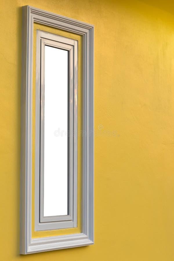 Sidofönster, lång vit ram med den gula väggen arkivfoton