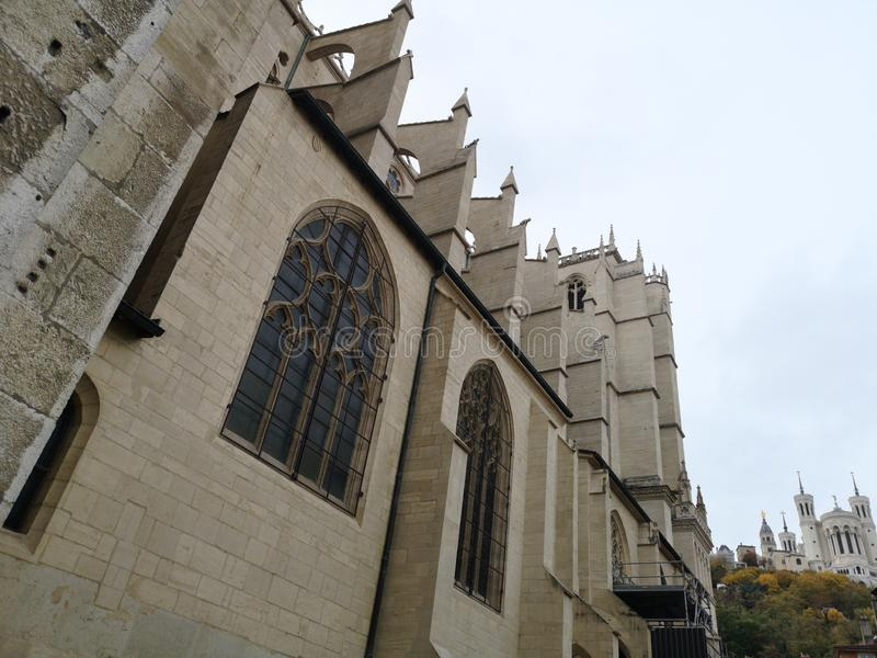 Sidofasadsikt av domkyrkan av St John det baptistiskt av Lyon och det Basilic av Notre Dame på bakgrunden, Frankrike royaltyfria bilder