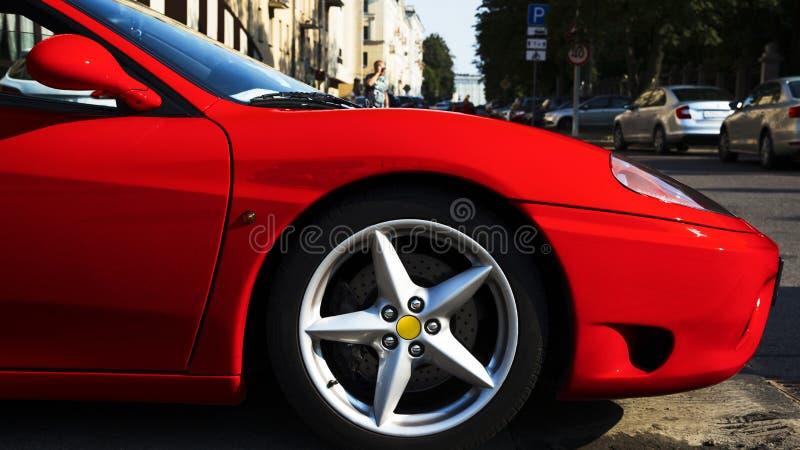 Sidofrämre sida av den skinande metalliska röda snabba bilen royaltyfria bilder