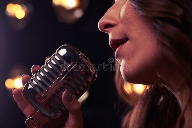 Sidonärbild av den retro mikrofonen för silver i strålkastare royaltyfri foto