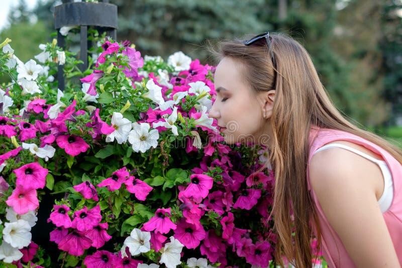 Sidoprofil av den unga kvinnan som luktar blomningar arkivbild