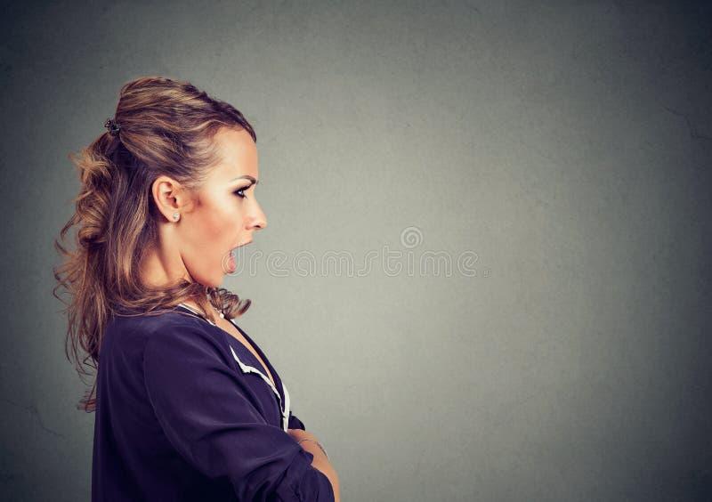 Sidoprofil av en förskräckt chockad kvinna arkivfoton