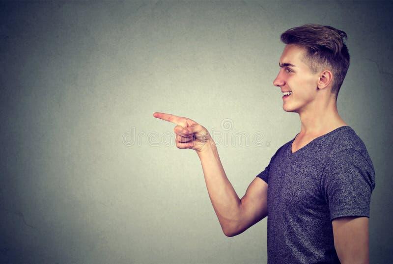 Sidoprofil av en skratta ung man som pekar fingret på någon royaltyfria foton