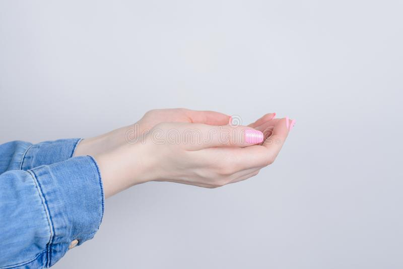Sidoprofilcloseupen kantjusterade fotoet av kupade händer som frågar för forgivennes isolerad grå bakgrund arkivbild