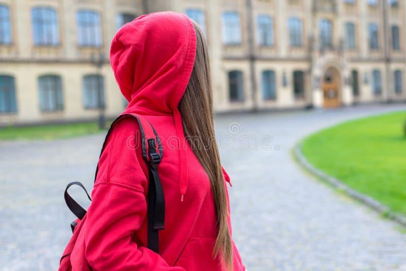 Sidoprofilfoto av den ledsna olyckliga ledsna ångerfulla tonåriga tonåringhipsterpersonen som tillbaka ser på universitetbyggnad royaltyfria bilder