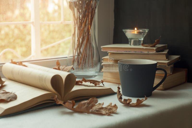 Sidor av en bok som bildar formen av hjärtan Passion för att läsa varm kopp te, ett fönster i bakgrunden Bokhjärta arkivfoto