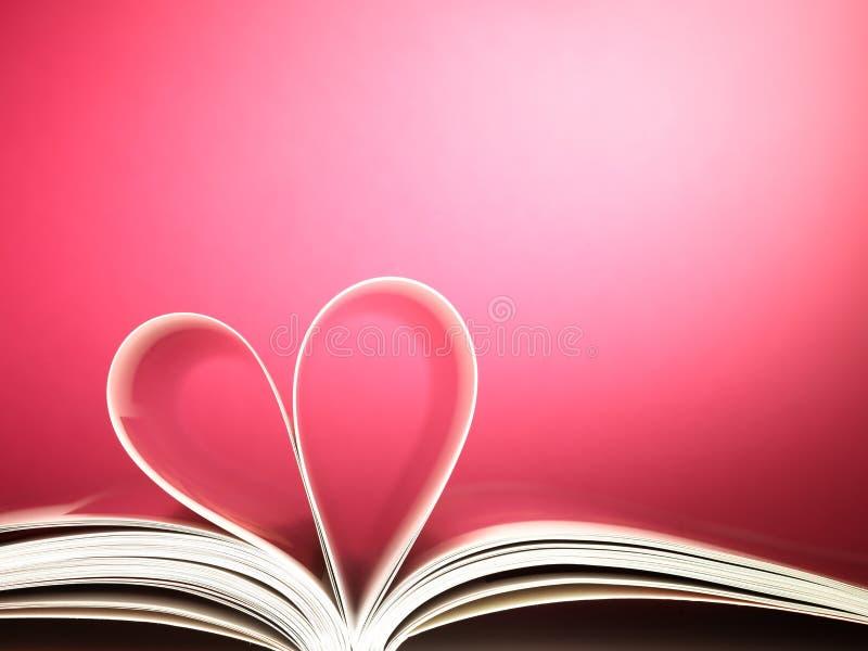 Sidor av en boka buktade in i en hjärta formar fotografering för bildbyråer