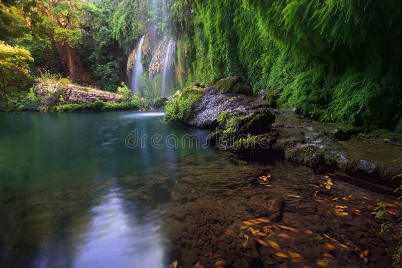 Sidor i en smaragdsjö med att bedöva vattenfall i djupt - den gröna skogen i naturliga Kursunlu parkerar, Antalya royaltyfri foto