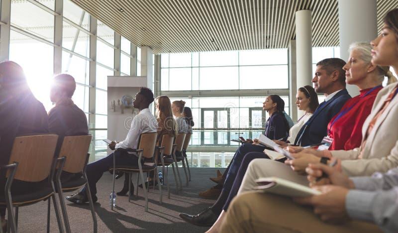 Sidosikt av affärsfolk som deltar i ett affärsseminarium royaltyfria foton