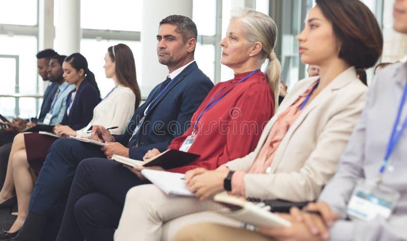 Sidosikt av affärsfolk som deltar i ett affärsseminarium royaltyfri fotografi