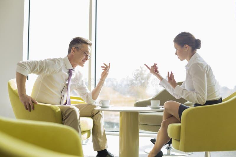 Sidosikt av affärsfolk som samtalar på lobbyen arkivfoto