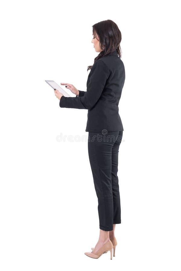 Sidosikt av affärskvinnan i den svarta dräkten som arbetar på minnestavladatoren royaltyfri foto
