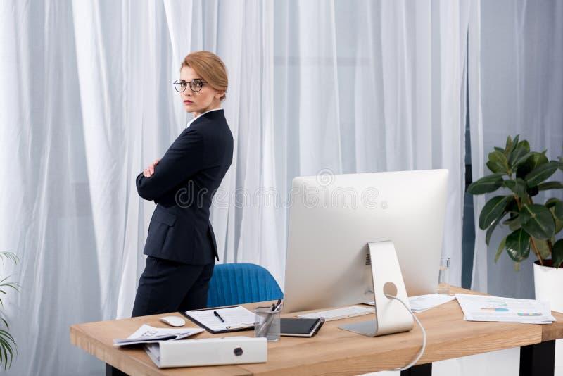sidosikt av affärskvinnan i dräktanseende på arbetsplatsen arkivbild