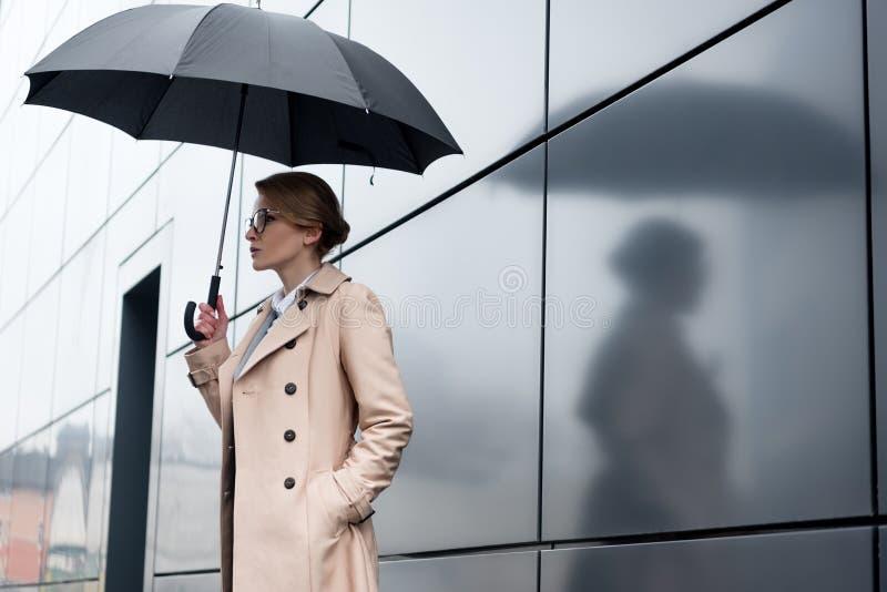 sidosikt av affärskvinnan i stilfullt lag med paraplyet arkivbilder