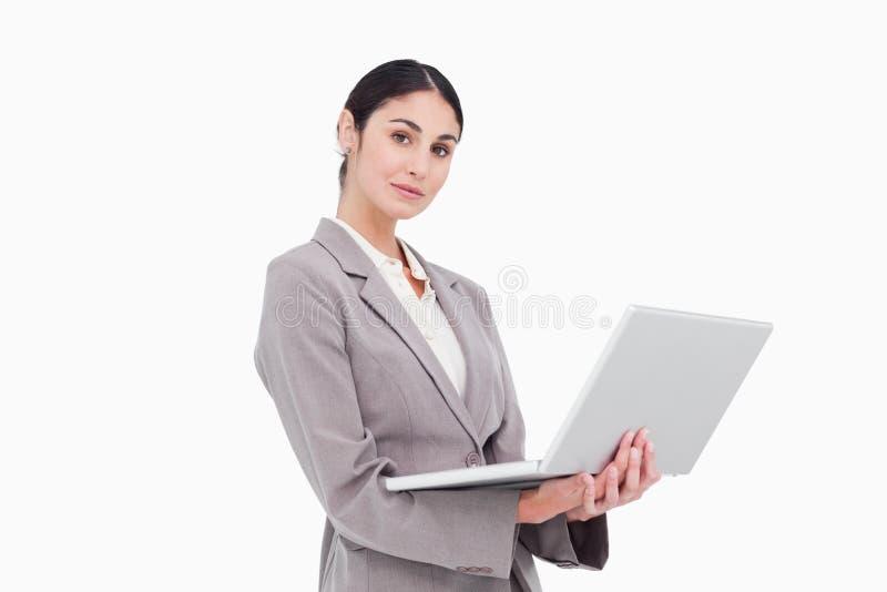 Sidosikt av affärskvinnan med bärbar dator
