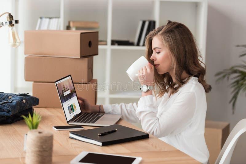 sidosikt av affärskvinnan som dricker kaffe, medan arbeta på bärbara datorn royaltyfri bild