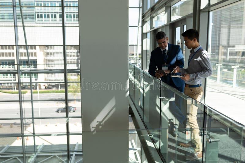 Sidosikt av affärsman som två ser ner en digital minnestavla på det första golvet av kontoret royaltyfria foton