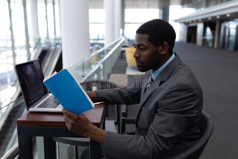 Sidosikt av afrikansk amerikanaffärsmannen med bärbara datorn som sitter på tabellen och läser en bok i modernt royaltyfria foton