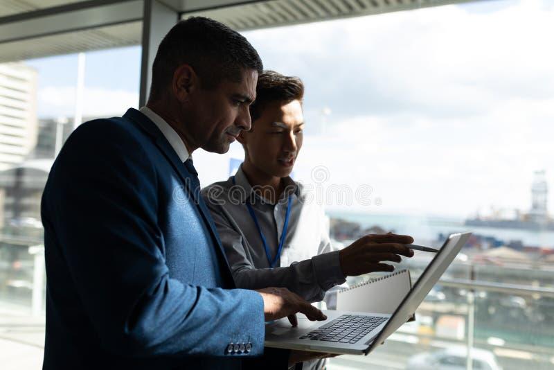 Sidosikt av anseendet för två affärsman på gångbanan för första golv och att arbeta på en bärbar dator i regeringsställning arkivfoto
