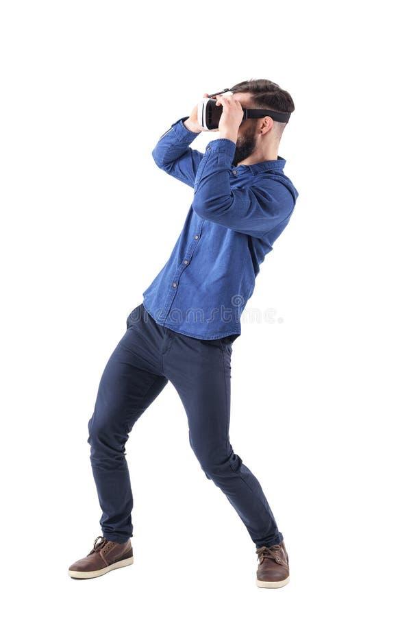 Sidosikt av att böja den unga mannen som har virtuell verklighetskyddsglasögonerfarenhet arkivfoton