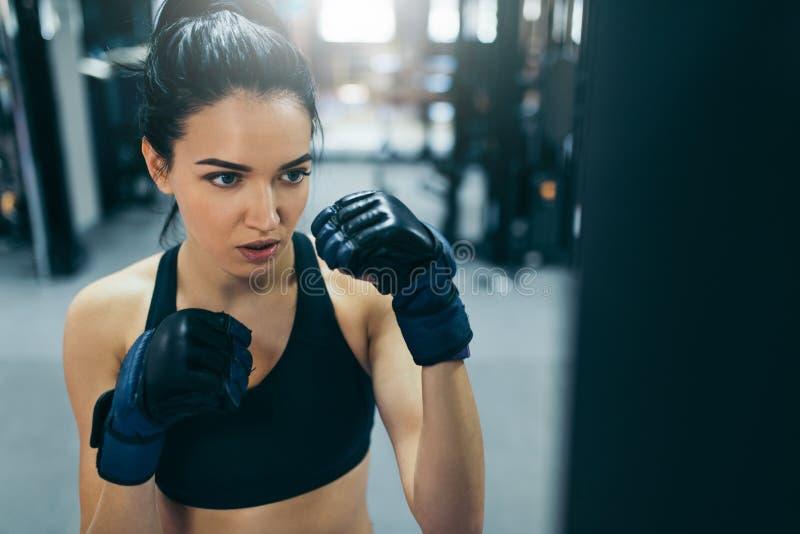 Sidosikt av att boxas den attraktiva brunettkvinnan som stansar en påse med kickboxing handskar i idrottshallgenomköraren Sport k royaltyfria bilder