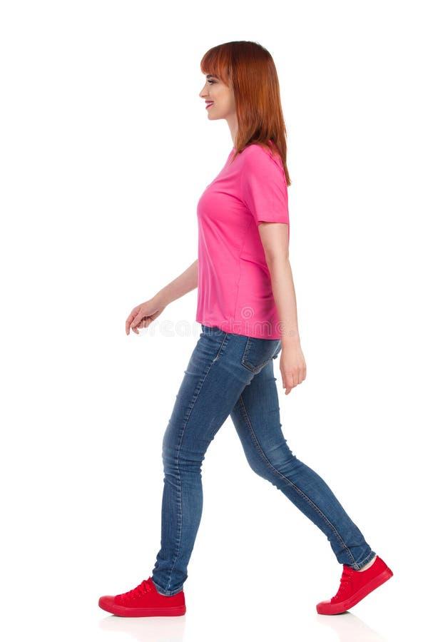 Sidosikt av att g? den h?rliga kvinnan i r?da gymnastikskor, jeans och rosa skjorta arkivfoto